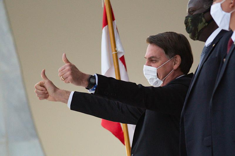 BRASILIA, BRAZIL - MAY 15: The President of Brazil Jair Bolsonaro waves to his supportersamidstthe coronavirus (COVID-19) pandemic at the Planalto Palace on May 15, 2020 in Brasilia. Brazil has over 202,000 confirmed positive cases of Coronavirus and 13,993 deaths. (Photo by Andressa Anholete/Getty Images)