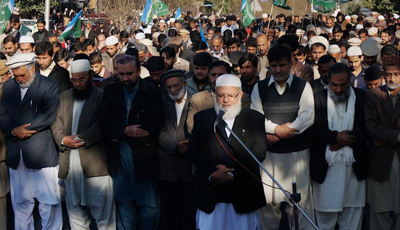 Liaquat Baluch, front, leader of Pakistan's religious party Jammat-e-Islami leads a prayer for Abdul Quader Mollah, leader of the Bangladesh's largest Islamic party Jamaat-e-Islami, in Islamabad, Pakistan, Friday, Dec. 13, 2013. Mollah was hanged Thursday for war crimes committed during Bangladesh's war of independence from Pakistan in 1971. (AP Photo/B.K. Bangash)