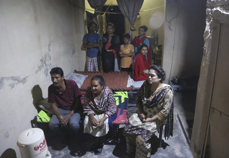 In this May 14, 2019, photo Pakistani Christian Natasha Masih, right front, sits with her family members during an interview in Faisalabad, Pakistan. Natasha begged her mother to bring her home from China, but it took an elaborate scheme devised by a small cabal of Christian men in her hometown of Faisalabad, in Pakistan's Punjab province, to orchestrate her escape from what began as an unhappy marriage, and ended in prostitution. (AP Photo/K.M. Chaudary)