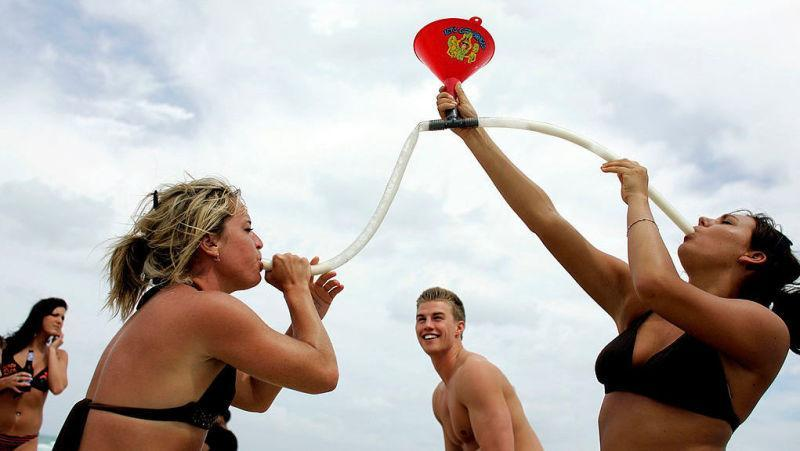 Two college women drinking from beer bong on beach