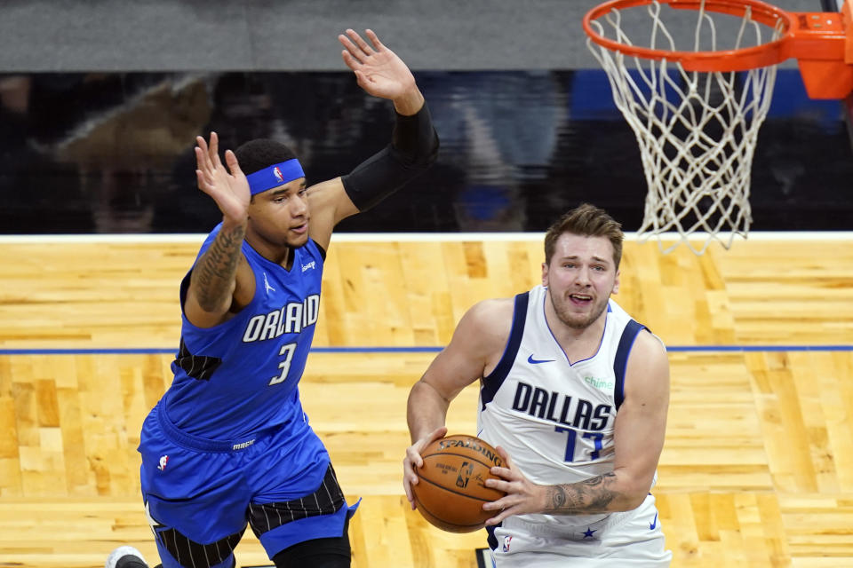 Dallas Mavericks guard Luka Doncic (77) goes past Orlando Magic forward Chuma Okeke (3) for a basket during the first half of an NBA basketball game, Monday, March 1, 2021, in Orlando, Fla. (AP Photo/John Raoux)