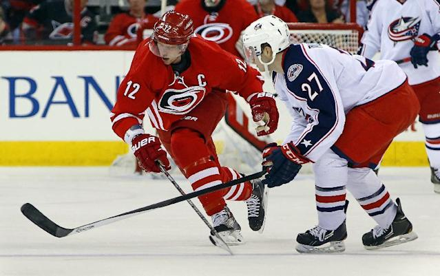 Carolina Hurricanes' Eric Staal (12) competes with Columbus Blue Jackets' Ryan Murray (27) during the second period of an NHL hockey game in Raleigh, N.C., Monday, Dec. 23, 2013. (AP Photo/Karl B DeBlaker)