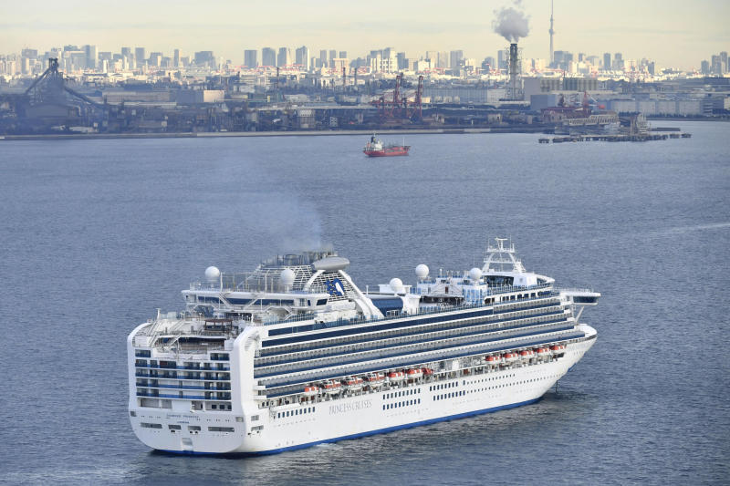 A cruise ship Diamond Princess anchor off the Yokohama Port upon arrival in Yokohama, near Tokyo Tuesday, Feb. 4, 2020. A person who was a passenger on the Japanese-operated cruise ship has tested positive for a new virus after leaving the ship in Hong Kong on Jan. 25. The ship returned to Yokohama carrying 3,000 passengers and crew members after making port calls in Vietnam, Taiwan and Okinawa. A team of quarantine officials and medical staff boarded the ship on Monday night and began medical checks of everyone on board, a health ministry official said on condition of anonymity, citing department rules. (Kyodo News via AP)