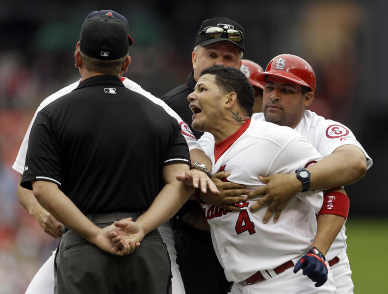 St. Louis Cardinals' Yadier Molina (4) is held back by his brother, first base coach Bengie Molina, while yelling at umpire Clint Fagan, left, after being thrown out of a baseball game by Fagan during the third inning against the San Francisco Giants, Sunday, June 2, 2013, in St. Louis. (AP Photo/Jeff Roberson)