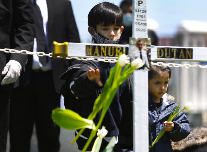 In this May 12, 2020 photo, Adriano Cuzco, a relative of Manuel Dutan, tosses flowers into the grave of Dutan, who died of COVID-19, at St. John's Cemetery in the Queens borough of New York. The Rev. Joseph Dutan lost his mentor and the first Catholic priest in the United States to die from the coronavirus. Days later, Dutan's own father, Manuel Dutan, contracted COVID-19. (AP Photo/Jessie Wardarski)