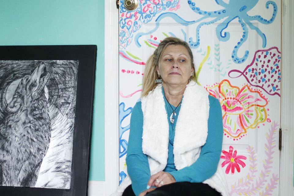 A middle-aged woman looking sad sitting in front of artwork.