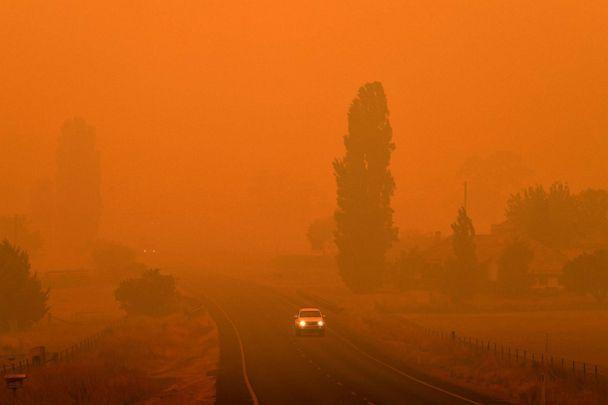 PHOTO: A car travels on a road through thick smoke from bush fires in Bemboka, in Australia's New South Wales state, Jan. 5, 2020. (Saeed Khan/AFP via Getty Images)