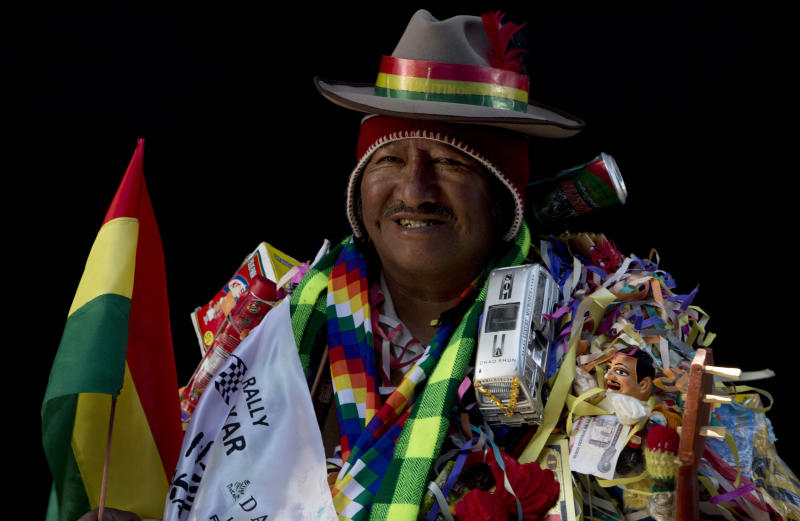 "In this Feb. 6, 2018 photo, Lino Reynaldo Chura, dressed as ""Ekeko,"" the god of prosperity, is covered in objects, including a miniature bus, during a portrait session on the sidelines of the annual Alasita Fair in La Paz, Bolivia. The 64-year-old artisan says his speciality is sewing miniature clothing for Barbies. ""I ask the Ekeko for good health, because the rest one attains by working,"" he said. Chura competed in this year's Ekeko costume competition. (AP Photo/Juan Karita)"