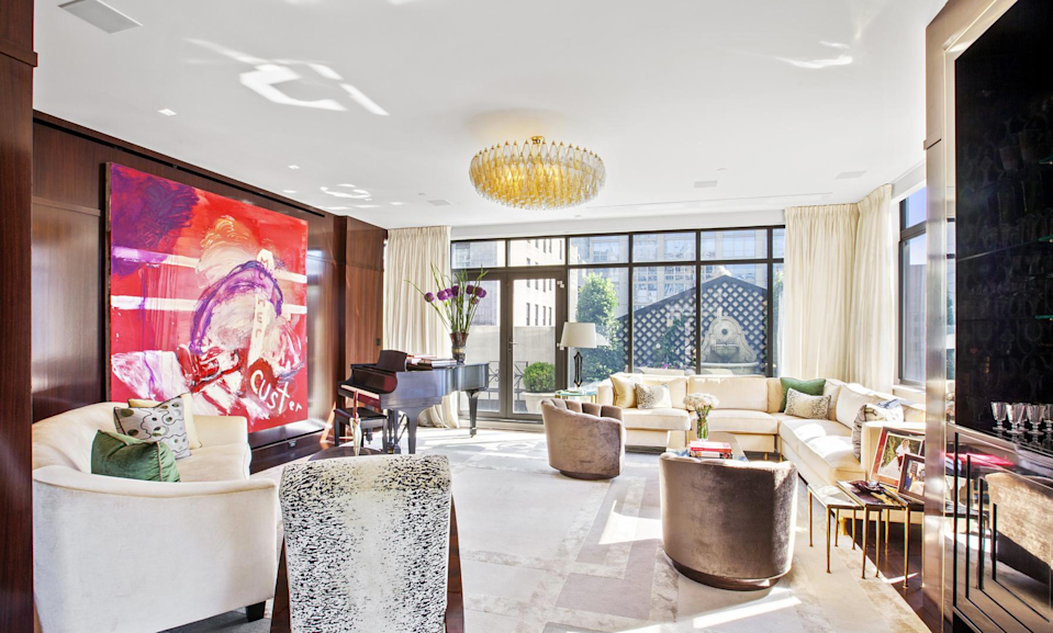 <p>The home's modern living room boasts floor-to-ceiling windows, Brazilian cherry wood floors, a Mahogany accent, as well as a high-definition projector and screen. (Douglas Elliman) </p>
