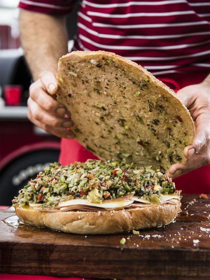 """<p>This crowd-pleasing sandwich has layers of meat, cheese and <a href=""""https://www.womansday.com/food-recipes/food-drinks/recipes/a56187/olive-salad-recipe/"""" rel=""""nofollow noopener"""" target=""""_blank"""" data-ylk=""""slk:olive salad"""" class=""""link rapid-noclick-resp"""">olive salad</a>.</p><p><span class=""""redactor-invisible-space""""><a href=""""https://www.womansday.com/food-recipes/food-drinks/recipes/a56186/new-orleans-style-muffulettas-recipe/"""" rel=""""nofollow noopener"""" target=""""_blank"""" data-ylk=""""slk:Get the New Orleans-Style Muffulettas recipe."""" class=""""link rapid-noclick-resp""""><em>Get the New Orleans-Style Muffulettas recipe.</em></a></span></p>"""