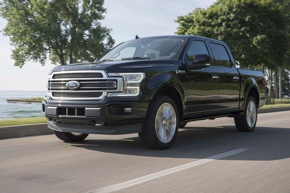 A black 2019 Ford F-150 Limited, a luxurious full-size pickup, on a coastal road.