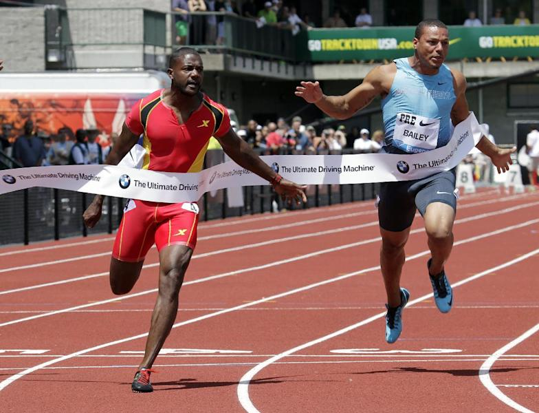 Justin Gatlin, left, hits the tape ahead of Ryan Bailey, to win the 100-meter race during the Prefontaine Classic track and field meet in Eugene, Ore., Saturday, June 1, 2013. Bailey finished third. (AP Photo/Don Ryan)