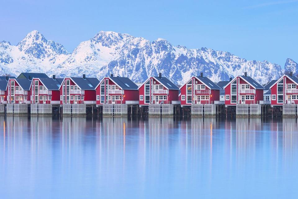 <p>Traditional wood houses in the fishing village of Svolvaer surrounded by snowcapped mountains.</p>