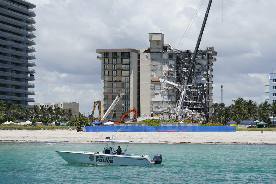 A Miami-Dade County Police boat patrols in front of the Champlain Towers South condo building, where search and rescue efforts continue more than a week after the building partially collapsed, Friday, July 2, 2021, in Surfside, Fla. (AP Photo/Mark Humphrey)