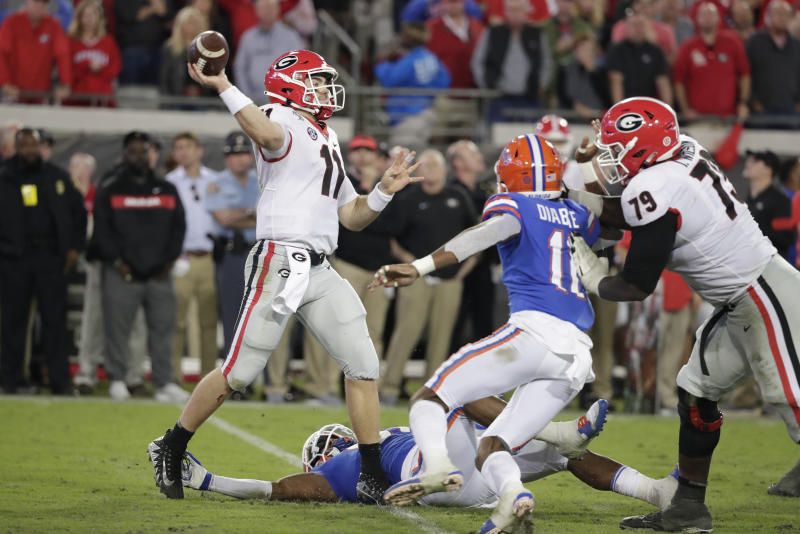 Georgia quarterback Jake Fromm (11) throws a pass during the second half as Florida linebacker Mohamoud Diabate, center, rushes on Saturday in Jacksonville, Fla. (AP Photo/John Raoux)
