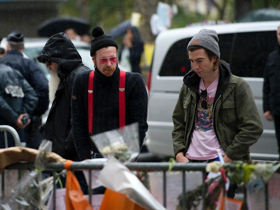 Jesse Hughes and Julian Dorio examine tributes to the victims of the attacks outside the Bataclan in December 2015 (AFP/Getty)