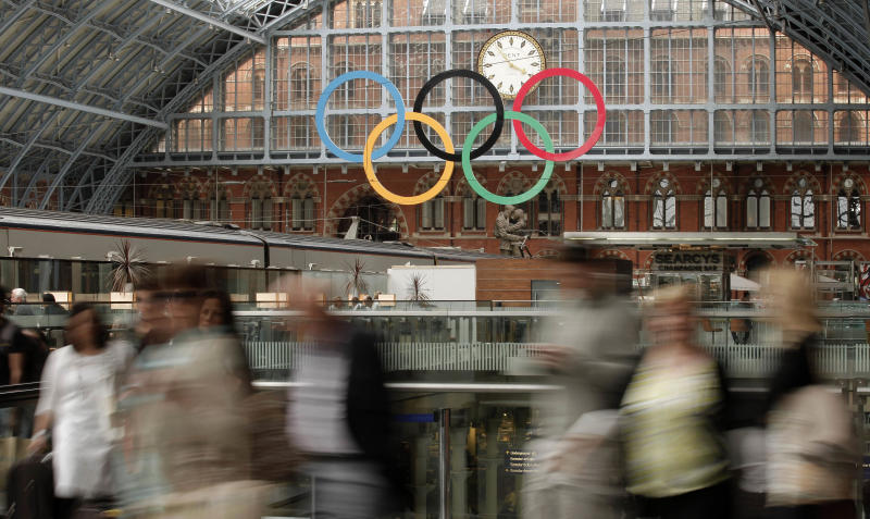 Passengers walk through St. Pancras International train station where the Olympic rings hang from the the ceiling, as London prepares for the 2012 Summer Olympics, Sunday, July 15, 2012. (AP Photo/Charlie Riedel)