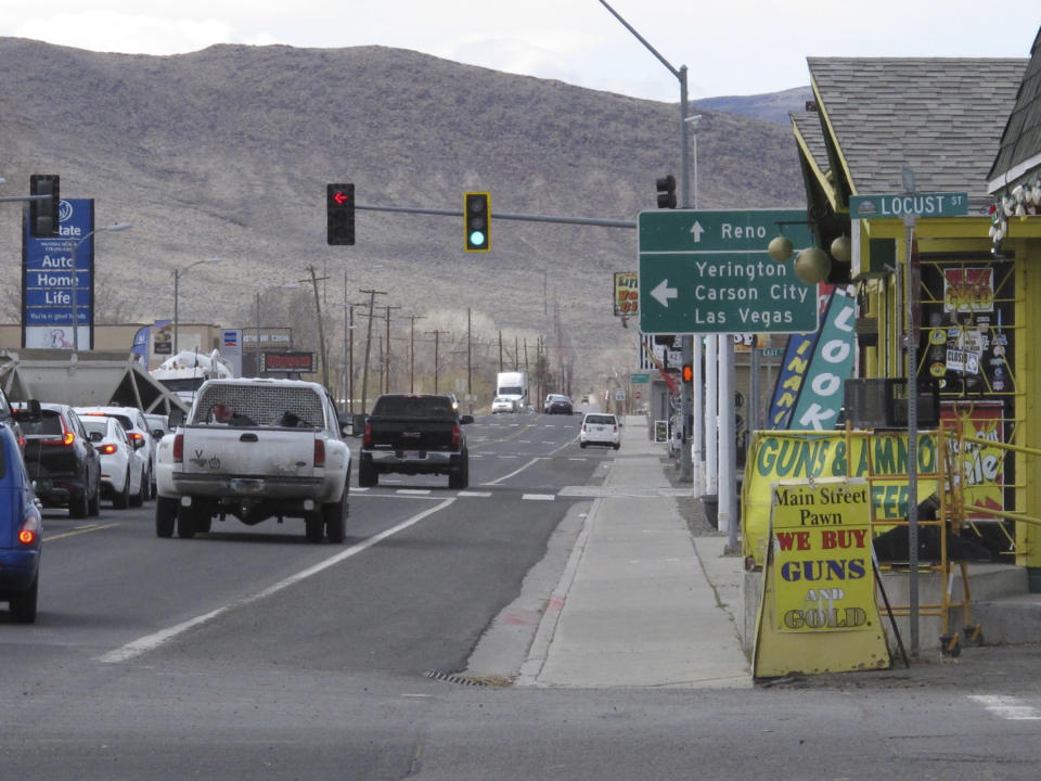 Traffic passes on Main Street in Fernley, Nev. about 30 miles east of Reno Thursday, March 18, 2021, The town founded a century ago by pioneers lured to the West with the promise of free land and cheap water is suing the U.S. government over plans to renovate an earthen irrigation canal that burst and flooded nearly 600 homes in Fernley in 2008. (AP Photo/Scott Sonner).