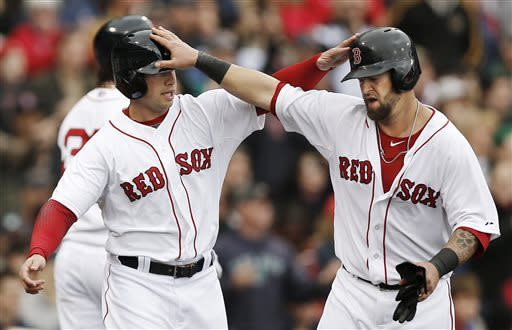 Boston Red Sox's Mike Napoli, right, and Daniel Nava congratulate each other after scoring on a throwing error by Tampa Bay Rays shortstop Yunel Escobar during the third inning of a baseball game at Fenway Park in Boston, Sunday, April 14, 2013. (AP Photo/Winslow Townson)