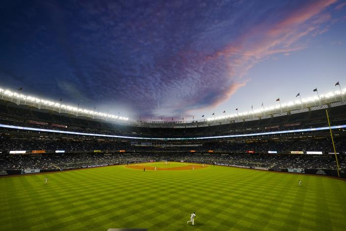 The New York Yankees play the Toronto Blue Jays under a pastel color sky during the fifth inning of the second game of a baseball doubleheader Thursday, May 27, 2021, in New York. (AP Photo/Frank Franklin II)