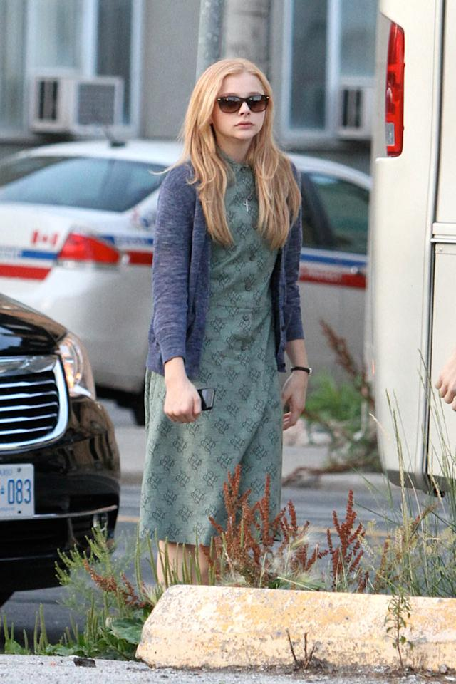 "Chloe Moretz is dressed in costume as ""Carrie White"" while on set filming the ""Carrie"" remake movie in Toronto, Canada."