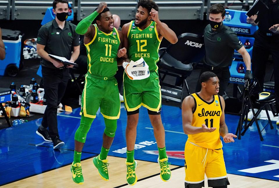 Oregon guard Amauri Hardy (11) and guard LJ Figueroa (12) and Iowa Hawkeyes guard Tony Perkins (11) react after a play in their second-round NCAA Tournament game.