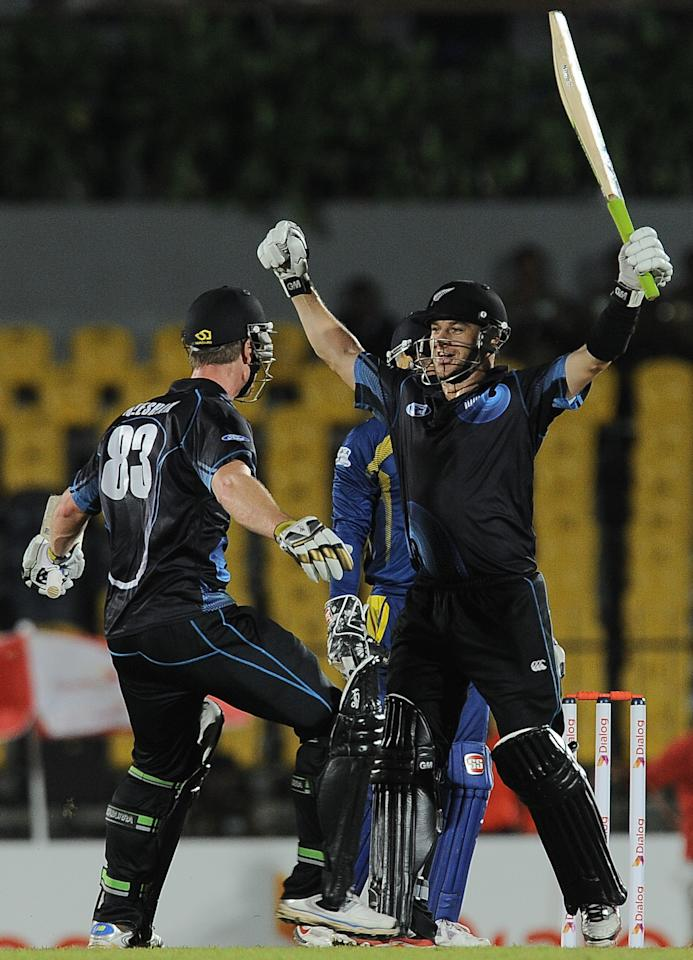 New Zealand batsmen Nathan McCullum (R) and James Neesham (L) celebrate after after victory in the second One Day International (ODI) cricket match between Sri Lanka and New Zealand at the Suriyawewa Mahinda Rajapakse International Cricket Stadium in the southern district of Hambantota on November 12, 2013. AFP PHOTO/ LAKRUWAN WANNIARACHCHI