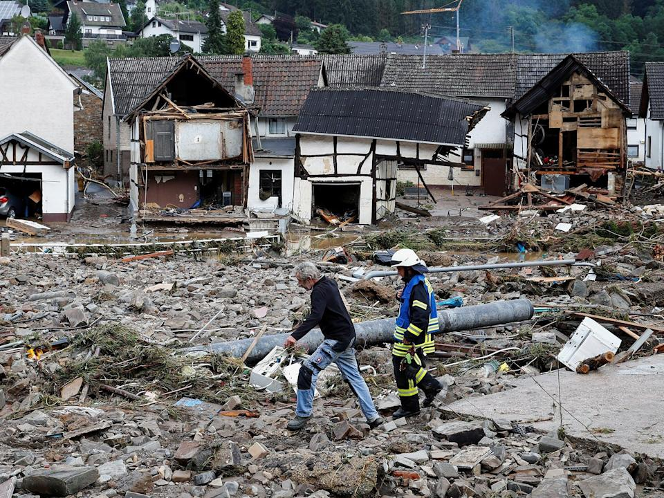 A man and firefighter walk through masses of debris following heavy rainfalls in Schuld, Germany (Reuters)