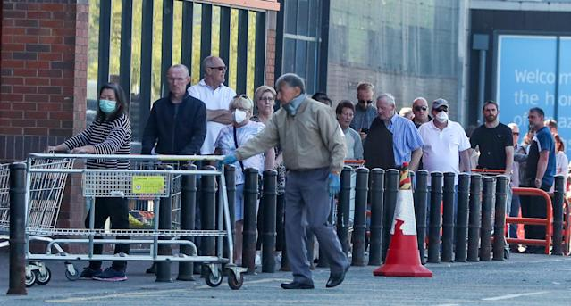 People queue outside a B&Q in Wallasey, Wirral on Saturday. (PA)