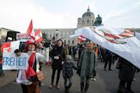 A demonstrator in Austrian capital Vienna waves a QAnon flag and carries a placard reading 'freedom'