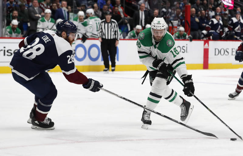 Dallas Stars center Jason Dickinson, right, reaches out to control the puck as Colorado Avalanche defenseman Ian Cole covers in the second period of an NHL hockey game Tuesday, Jan. 14, 2020, in Denver. (AP Photo/David Zalubowski)