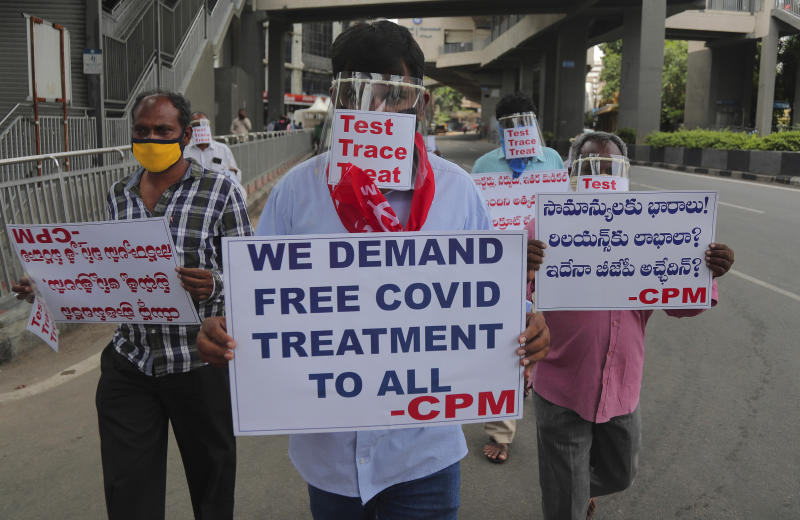 Activists of Communist Party of India Marxist wearing face shields and hold placards during a protest asking the state government to increase testing and free treatment for all COVID-19 patients in Hyderabad, India, Monday, June 29, 2020. Governments are stepping up testing and warily considering their next moves as the number of newly confirmed coronavirus cases surges in many countries. India reported more than 20,000 new infections on Monday.  (AP Photo/Mahesh Kumar A.)