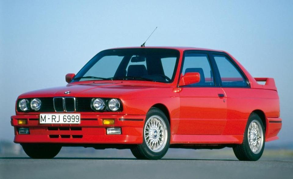 """<p>Like many great, rare, and collectible cars, the first BMW M3 exists because of racing. In the 1980s, the FIA required Group A race cars to have a street-legal counterpart. According to the rules, BMW had to build 5000 M3s in a 12-month period to qualify for racing. The M3 debuted at the Frankfurt auto show in 1985, BMW built the cars, and the M3 became a European Touring Car champion. </p><p>Radically different from the regular E30 3-series of the day, <a href=""""http://www.caranddriver.com/reviews/1988-bmw-m3-road-test-review"""" rel=""""nofollow noopener"""" target=""""_blank"""" data-ylk=""""slk:the M3"""" class=""""link rapid-noclick-resp"""">the M3</a> came with its own flared fenders, body kit, and large rear spoiler. The windshield and rear window were flush mounted, and the rear window was installed at a more rakish angle. The drag coefficient fell from a claimed 0.37 to 0.33. </p>"""