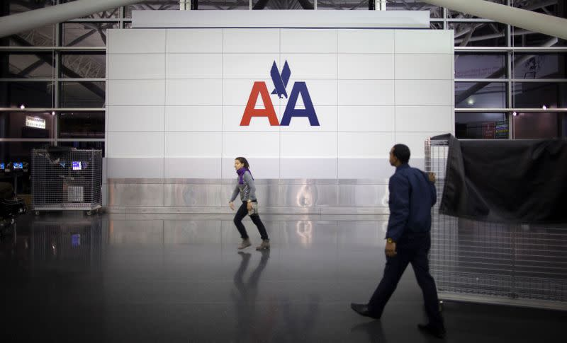 FILE PHOTO: People walk past an American Airlines logo at John F. Kennedy (JFK) airport in in New York