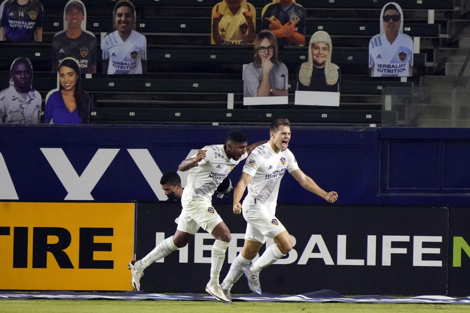 Los Angeles Galaxy's Kai Koreniuk, right, celebrates his goal with teammate Carlos Harvey during the second half of an MLS soccer match against the Vancouver Whitecaps, Sunday, Oct. 18, 2020, in Carson, Calif. (AP Photo/Marcio Jose Sanchez)