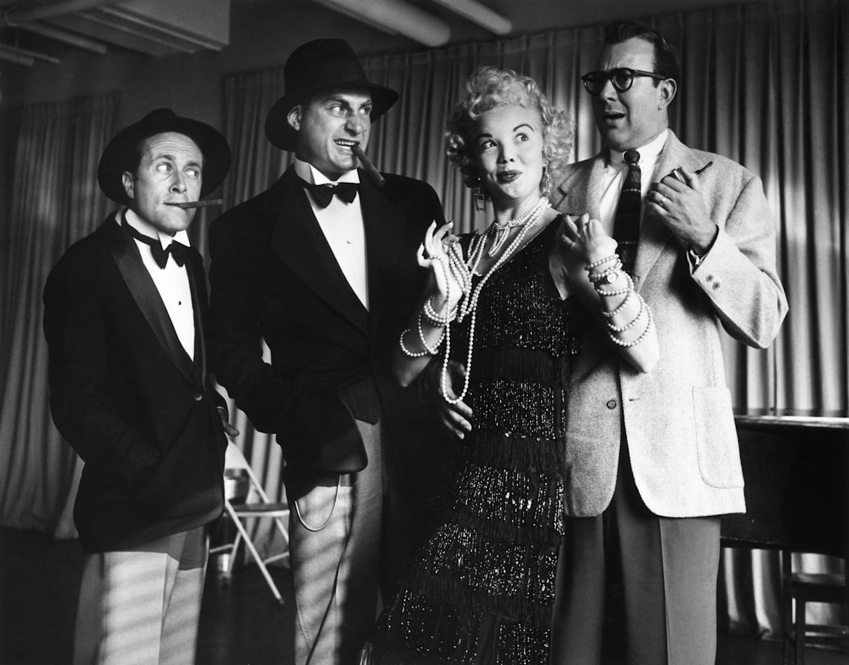 circa 1954:  American actors Howard Morris, Sid Caesar, Nanette Fabray and Carl Reiner posing in costume during a rehearsal for the television series, 'Caesar's Hour'. Fabray wears a 1920s flapper costume. Morris and Caesar wear the top half of a tuxedo with a hat while smoking cigars.  (Photo by Hulton Archive/Getty Images)