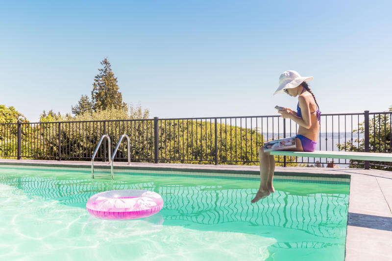 A teen sits on a diving board playing on her phone.