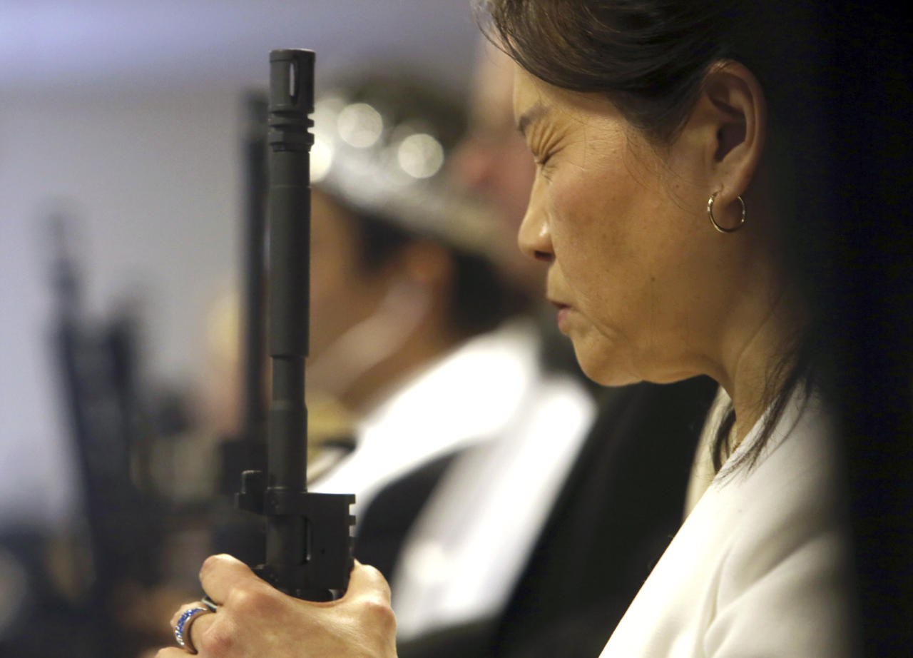 <p>A woman holding an unloaded weapon closes her eyes during services at the World Peace and Unification Sanctuary, Wednesday Feb. 28, 2018 in Newfoundland, Pa. (Photo: Jacqueline Larma/AP) </p>