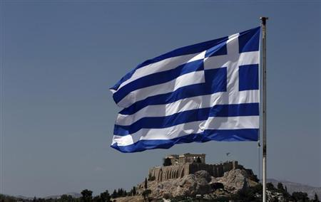 A Greek flag flutters in front of the Acropolis hill in Athens