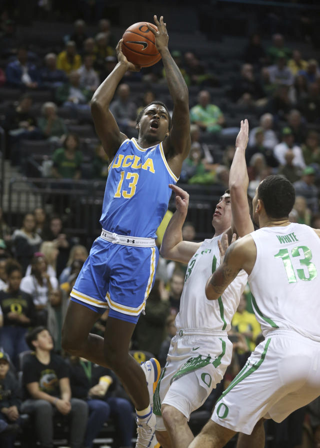 UCLA's Kris Wilkes, left, shoots over Oregon's Payton Pritchard, center, and Paul White, right, during the the first half of an NCAA college basketball game Thursday, Jan 10, 2019, in Eugene, Ore. (AP photo/Chris Pietsch)