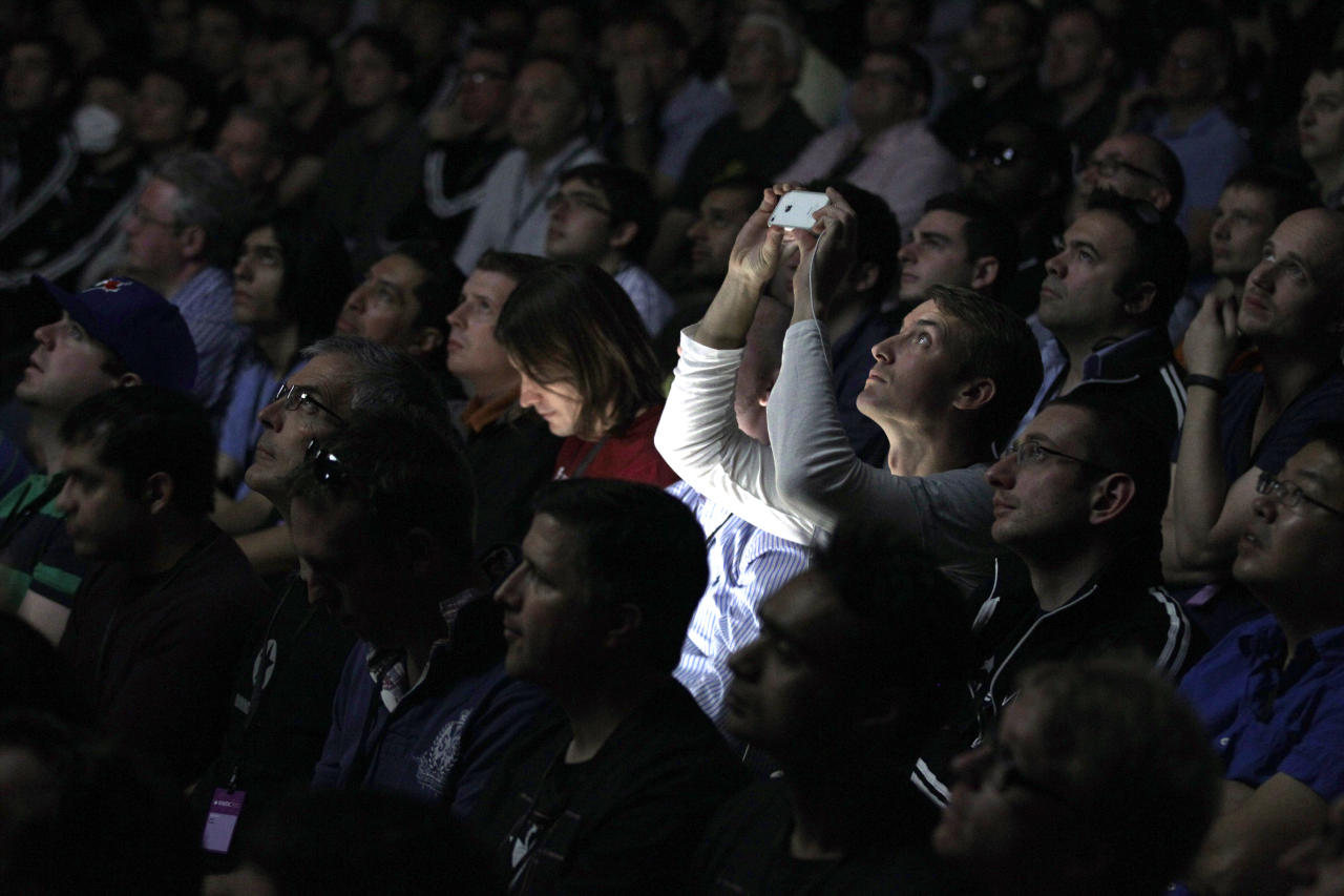 Attendees watch a video presentation on new products during the Apple Developers Conference in San Francisco,  Monday, June 11, 2012. In recent years, Apple Inc. has used its Worldwide Developers Conference as an opportunity to announce new software for the iPhone, iPad and iPod Touch. (AP Photo/Marcio Jose Sanchez)