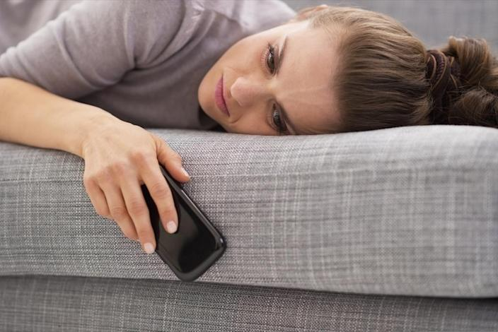 A woman laying on sofa holding phone.