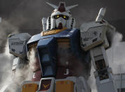 """A full-size model of Japan's robot animation character """"Gundam"""" emits mists and lights up its eyes during a demonstration in front of a shopping mall in Tokyo May 7, 2012. The 18-meter-tall """"Gundam"""" was installed to promote its entertainment facility """"Gundam Front Tokyo"""" which opened last month. REUTERS/Kim Kyung-Hoon (JAPAN - Tags: SOCIETY BUSINESS ENTERTAINMENT)"""