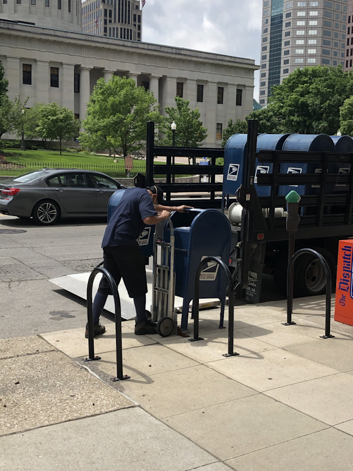 A Postal worker removes mailboxes in downtown Columbus, Ohio on May 29, 2020. He said they were being removed because of damage in the area after protests the night before. The boxes were returned Aug. 21.