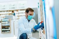 Male pharmacist with protective mask and face shield on his face, working at pharmacy.