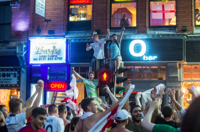 <p>Not everyone sat despondently – these fans in Birmingham cheered for England despite the loss. (SWNS) </p>