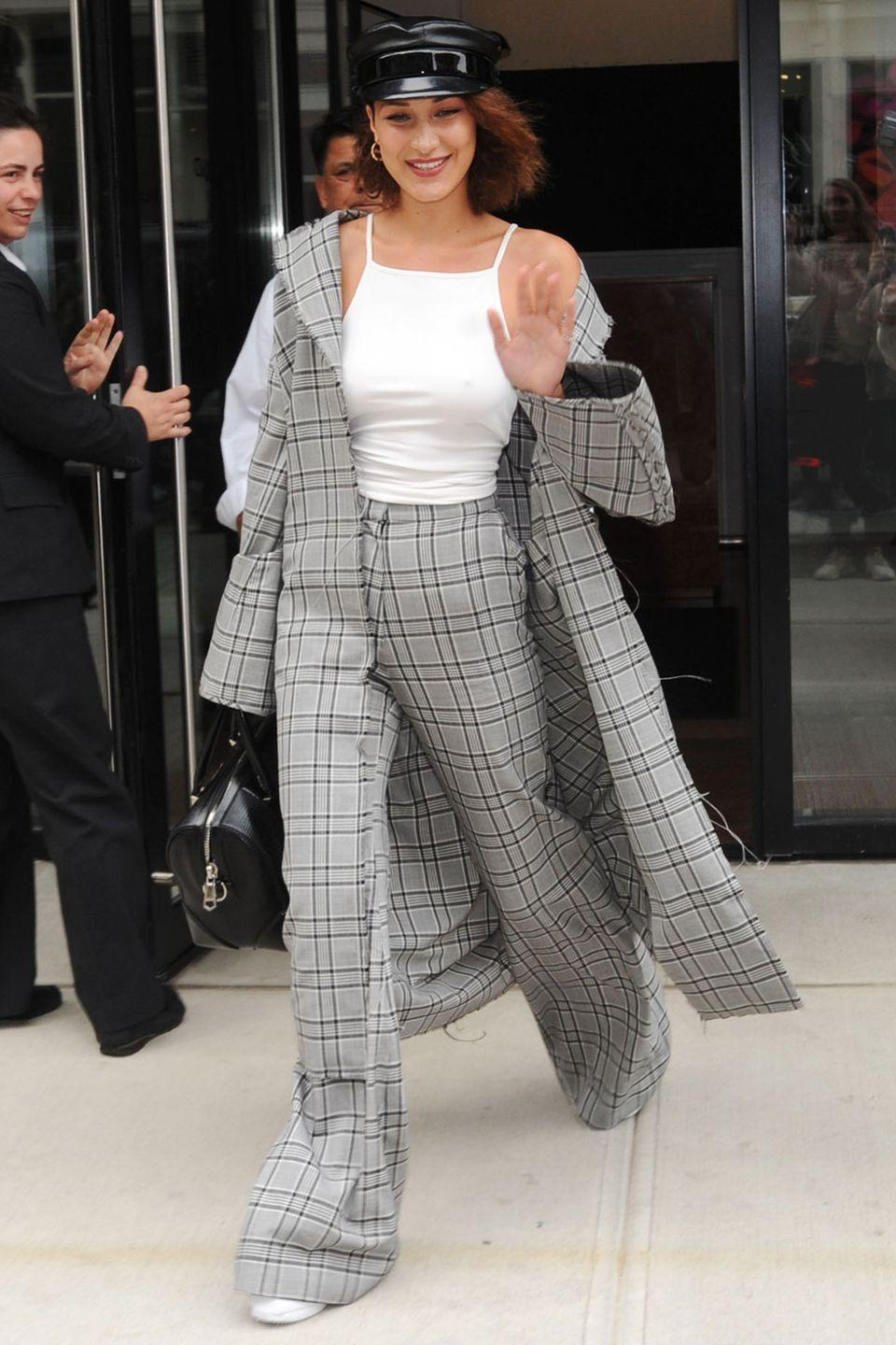 <p>In an oversized gray plaid trench and trousers from Zimmermannn, white tank top, white sneakers and conductor hat while out in NYC.</p>