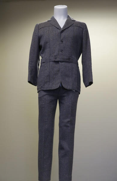 """This photo taken Monday, Dec. 2, 2013, shows the grey wool suit Gene Kelly wore in the movie """"Singin' in the Rain"""" is displayed at at Heritage Auctions in Dallas. Kelly's suit was purchased by the theme restaurant Planet Hollywood International for more than $106,000. Kelly wore the suit for the soggy featured dance in the 1952 movie musical. (AP Photo/LM Otero)"""