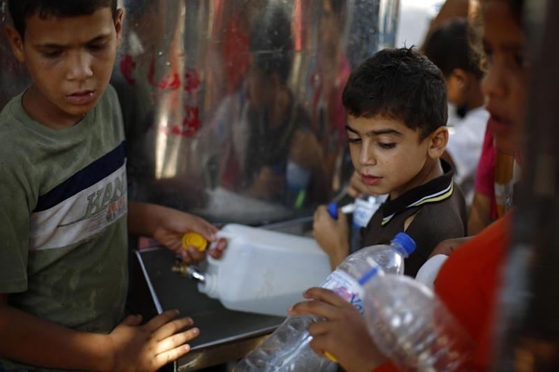 Palestinians displaced due to Israeli bombardment on the Gaza Strip, fill plastic bottles and water containers with drinking water at a UN school which is housing them on August 8, 2014 (AFP Photo/Mohammed Abed)