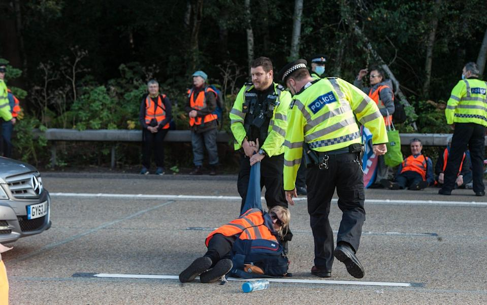 Police remove activists from the motorway as protestors from Insulate Britain block the M25 motorway near Cobham in Surrey on September 21, 2021 - Guy Smallman/Getty Images